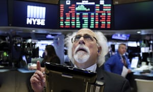 Trader Peter Tuchman watches screens on the floor of the New York Stock Exchange after the rate decision on Wednesday in New York, New York.