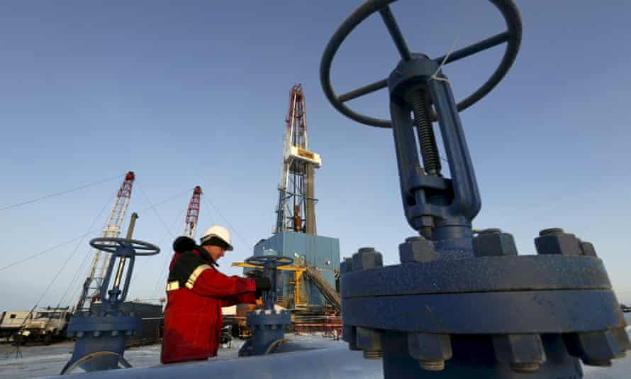 A worker checks an oil pipe at the Imilorskoye oil field in Siberia, Russia