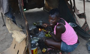 A teenage girl is cooks the family's evening meal inside a makeshift tent of flattened cardboard boxes and cloth at a borderland encampment outside Anse-à-Pitres, Haiti.
