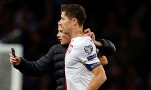 Robert Lewandowski is stunned as a fan comes on to the the pitch to take a selfie with the Poland player