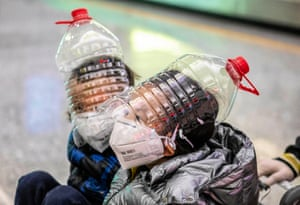 Guangzhou, China: children wear improvised face protection made from water bottles at Guangzhou airport as international airlines suspended or limited flights to and from China during the coronavirus outbreak