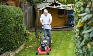 A senior man mowing a lawn