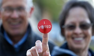 """A couple shows off their """"I Voted"""" sticker as they leave Wasatch elementary school after casting their ballot in Provo, Utah."""