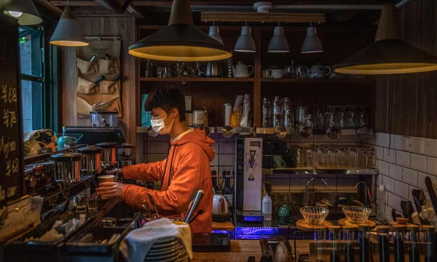 A man wearing a protective face mask works at a coffee shop in Wuhan after the lockdown is ended.