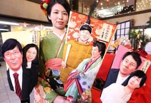 A Kyugetsu employee displays hagoita – ornamental wooden rackets – decorated with images of Shinjiro Koizumi and Christel Takigawa (R), Emperor Naruhito and Empress Masako (C) and newlywed couple Ryota Yamasato and Yu Aoi (L) for 2019's news makers at the company's showroom.