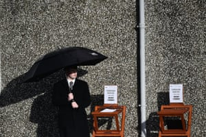 Ballybricken, Ireland: An undertaker stands beside a book of condolence outside St Ailbe's parish church during the Cranberries singer Dolores O'Riordan's funeral