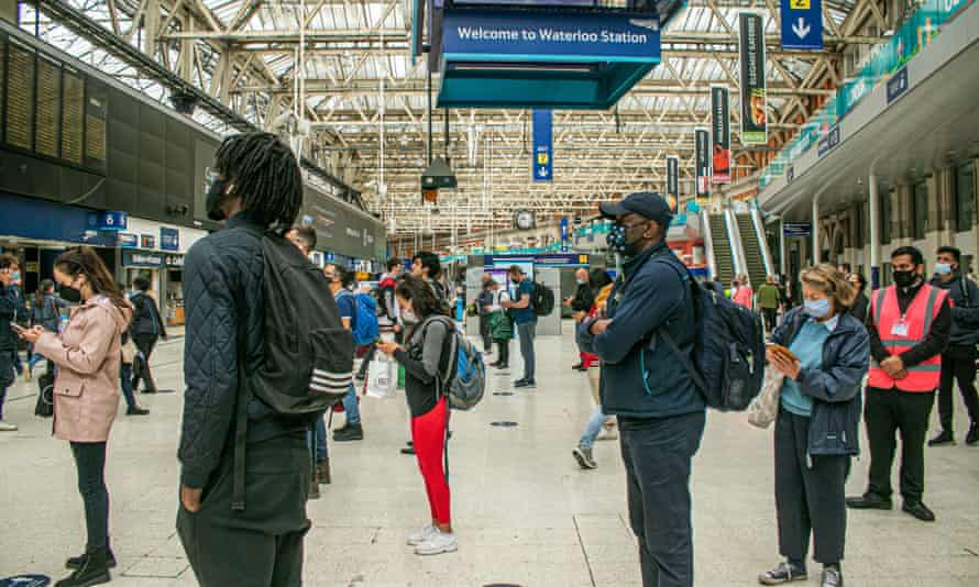 Masked rail passengers stand in wait at Waterloo station