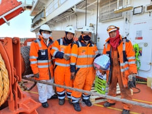 Four Filipino seafarers onboard a ship in port at Rotterdam holding gift bags