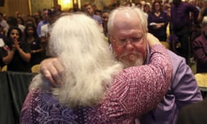 Susan Bro and Mark Heyer embrace during a memorial for their daughter.