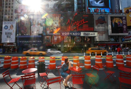 A woman enjoys her morning coffee in the middle of Broadway in Times Square after it was closed to cars.