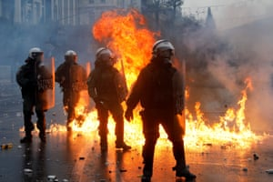 Riot police in Athens stand among flames while facing protesters in Athens
