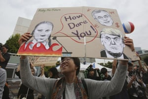 Seoul, South Korea An environmental activist holds a board showing images of Swedish climate activist Greta Thunberg and South Korean President Moon Jae-in and US President Donald Trump, bottom right, as she marches toward the presidential Blue House