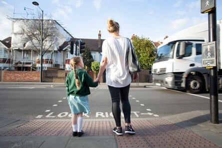 Children stand nearby a busy road with air pollution from trucks .