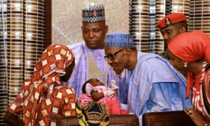 Amina Ali Darsha Nkeki hands her child to President Muhammadu Buhari in Abuja.