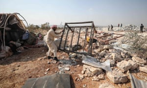 A Syrian man clears debris at the site of helicopter gunfire, which is thought to have killed nine people near Barisha.