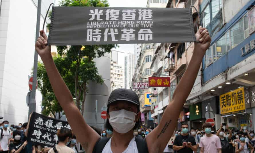 A protester holding a banner reading 'Liberate Hong Kong: revolution of our time'