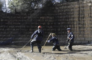Members of the Los Angeles County Fire Department Search and Rescue crew work in mud looking for missing people