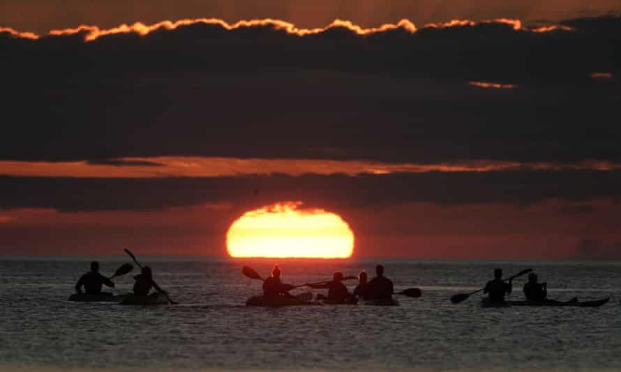 Kayakers watching the sunrise early on Saturday morning at Cullercoats bay in North Tyneside.