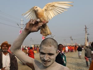 A Sadhu walks with his pet bird after taking a holy bath