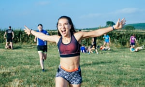 A girl in running kit running with her arms open and shouting as if she's going through the finishing line
