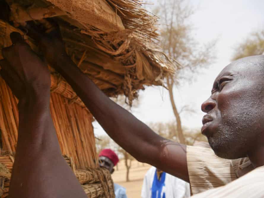 A Droum farmer opens his millet store.