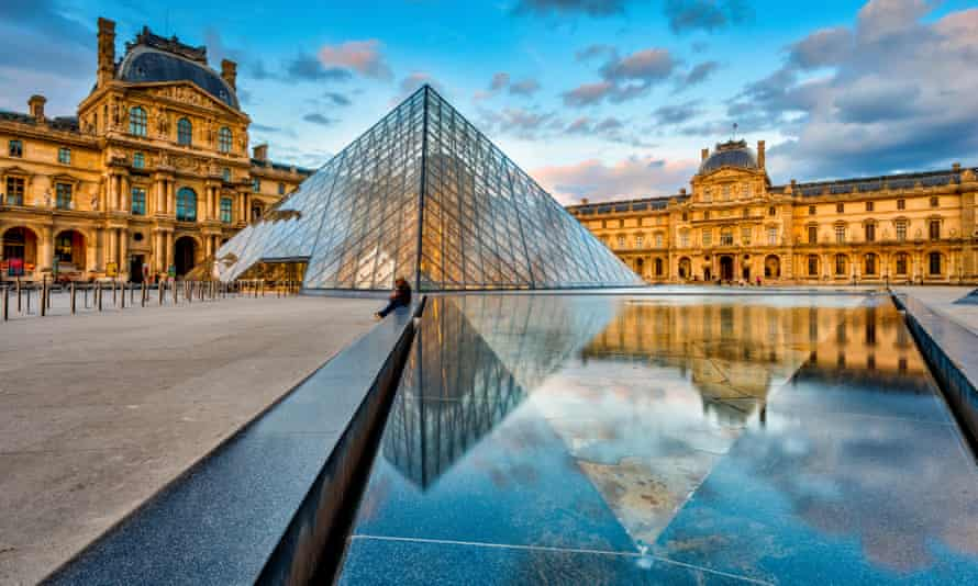 There is a blue sky with the reflection of the Museum Louvre with the Pyramid