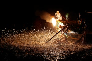 The fire is waved over the side of the fishing boat.