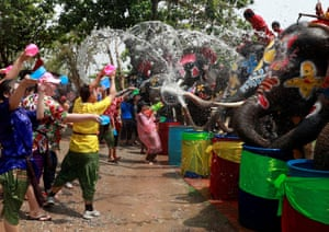 Elephants and people play with water as part of celebrations for the water festival of Songkran