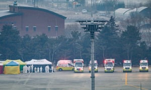 Quarantine personnel and ambulances are ready to receive South Koreans arriving from Wuhan, China, at Gimpo International Airport in western Seoul, South Korea