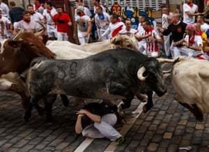 A man tries to shelter as a bull jumps over the top of him