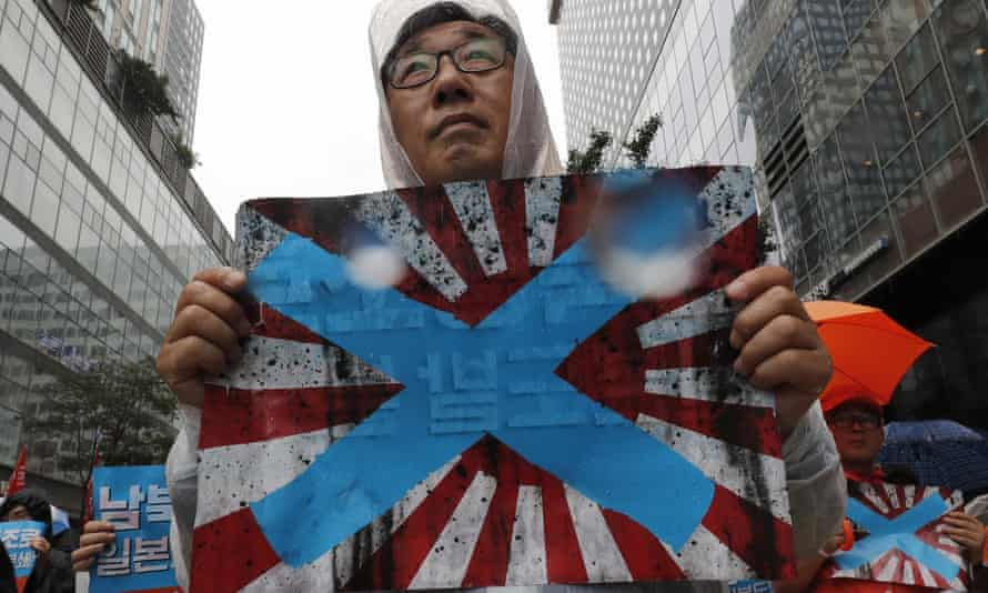 South Korean protesters hold Japanese rising sun flags during a rally to mark the South Korean Liberation Day from Japanese colonial rule in August.
