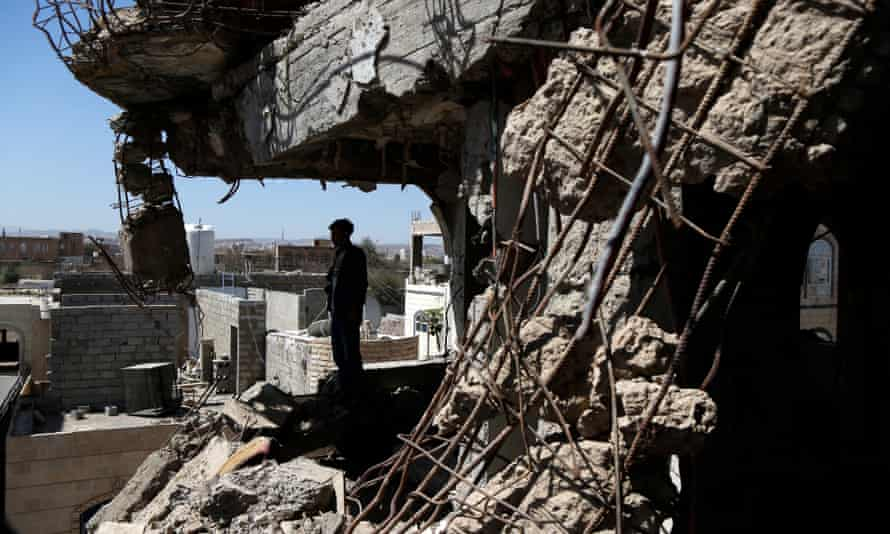 A Yemeni man inspects a house destroyed in an airstrike carried out during the war by the Saudi-led coalition's warplanes.
