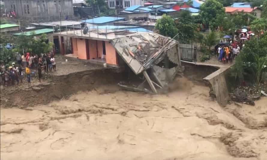 A house collapses after its foundations were washed away as the Comoro river floods in Dili, Timor-Leste.
