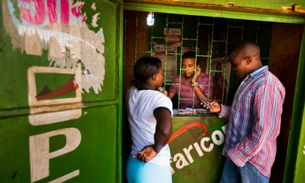 Residents transfer money using the M-Pesa banking service at a store in Nairobi.