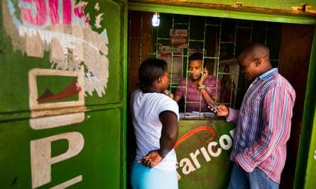 Residents transfer money using the M-Pesa banking service at a store in Nairobi, Kenya.