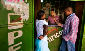 People transfer money using the M-Pesa mobile banking service at a store in Nairobi, Kenya, in 2013.