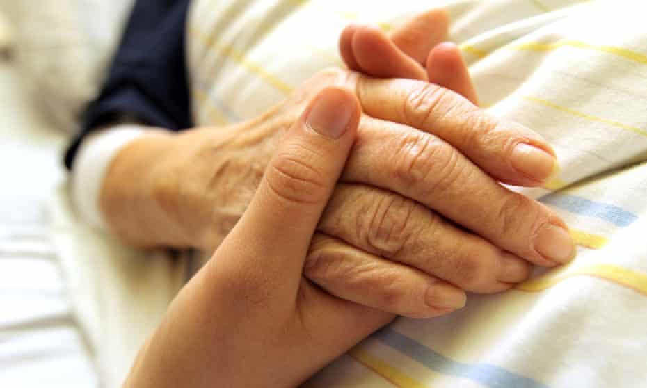 An older woman's hand being held