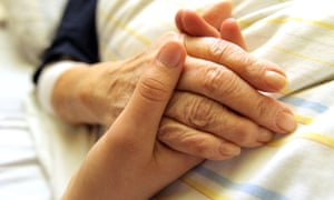 young woman holds older woman's hand