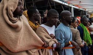 Refugees wait on the deck of a Spanish vessel after being rescued off the Libyan coast in February.