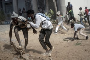 Demonstrators take cover during clashes with riot police at a protest in support of main opposition leader and former presidential candidate Ousmane Sonko in Dakar.