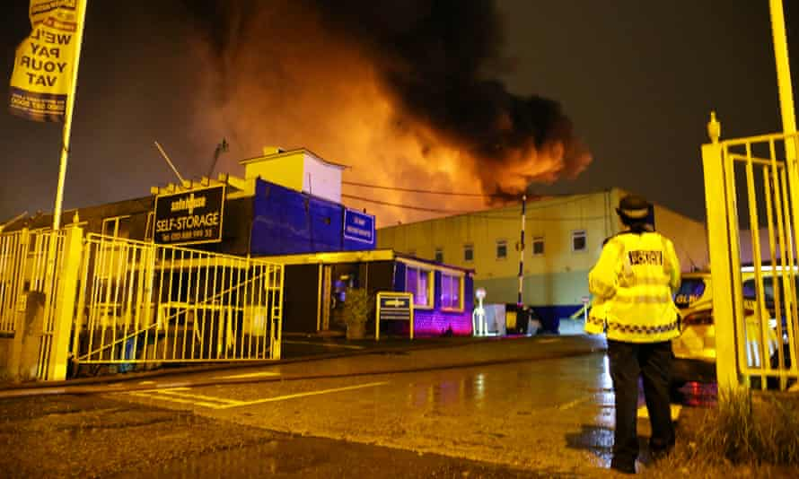 Police stand guard as firefighters (unseen) tackle a fire at a warehouse in Tottenham, north London.