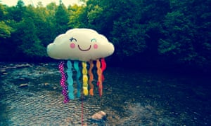 Cloudhelium balloon with face standing on river