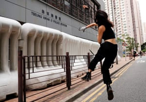 A protester throws a stone at a police station in Tseung Kwan O residential district.