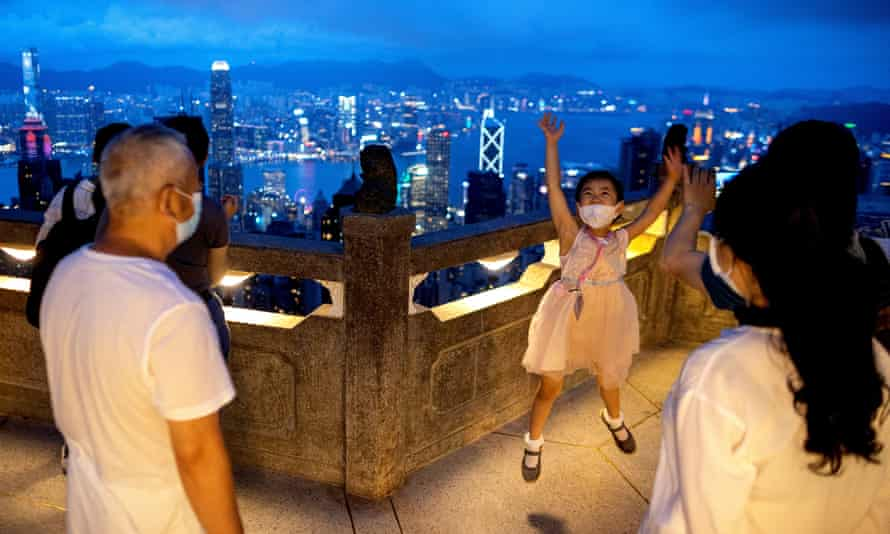 A girl jumps for a photograph on a viewing platform overlooking Hong Kong