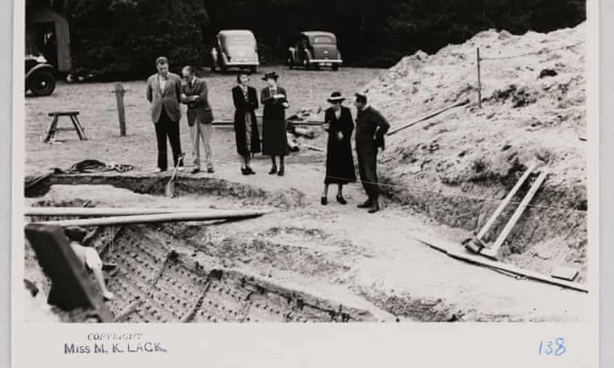 Black and white photo of people gathered around excavated ship