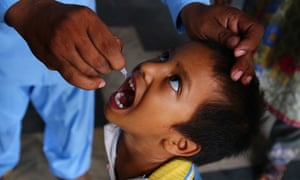 A health worker administers a polio vaccination to a child, in Karachi, Pakistan