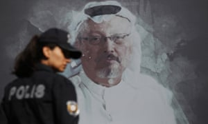 A Turkish police officer walks past a picture of Jamal Khashoggi prior to a ceremony, near the Saudi Arabia consulate in Istanbul, marking the one-year anniversary of his death, on 2 October.