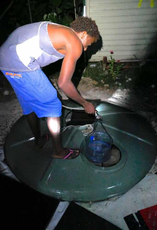 A detainee gets water from a makeshift well inside the Manus Island detention centre.