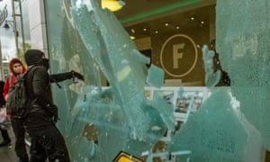 A protester smashes the front window of Foxton, an estate agency, which is perceived as part of the problem of gentrification of Brixton.