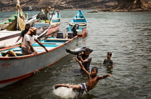 A young boy plays in the sea as fishermen unload fish they caught earlier, at a fish market in the port city of Aden, on 8 September, 2019.